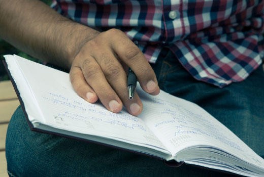 Close-up shot: the hand of a young migrant. He is making notes in a diary.