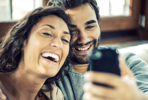 A woman and a man take a selfie with a smartphone.